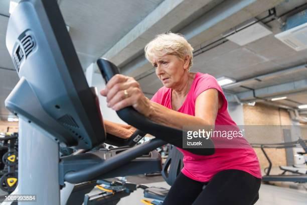 senior woman exercising on cycling machine at rehabilitation gym - izusek stock pictures, royalty-free photos & images