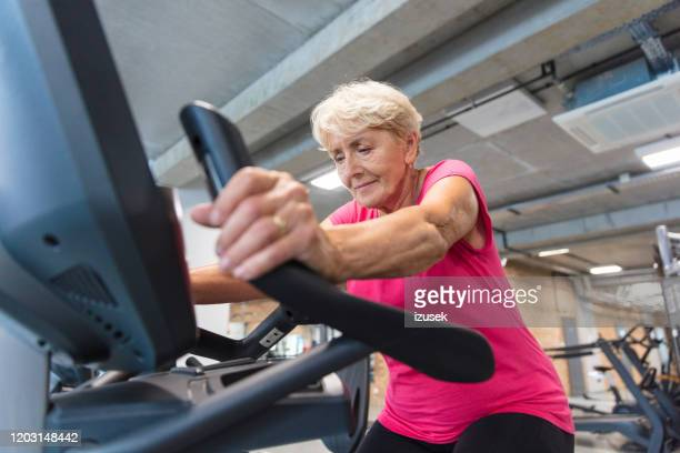 senior woman exercising on cycling machine at rehabilitation gym - leisure facilities stock pictures, royalty-free photos & images
