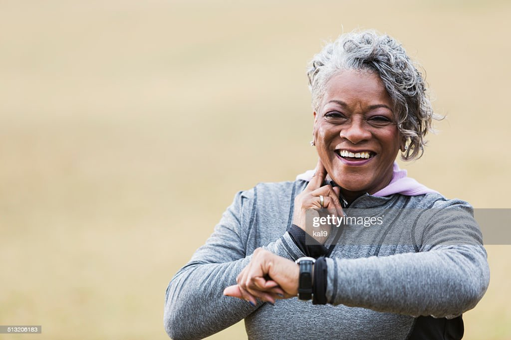 Senior woman exercising, taking pulse : Stock Photo