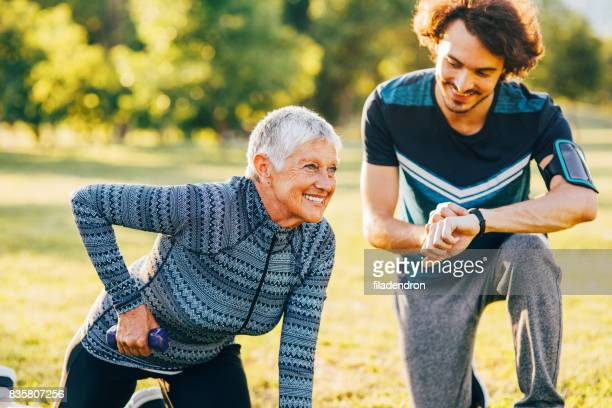 Senior woman exercising with a personal trainer outdoors