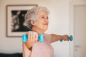 senior woman lifting weights working out