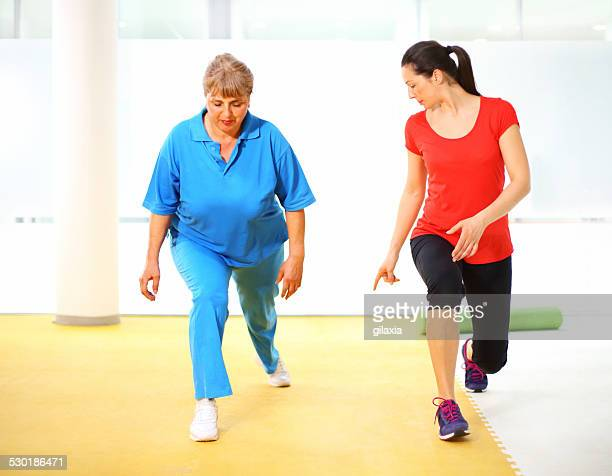 senior woman exercising with instructor. - chubby legs stock photos and pictures