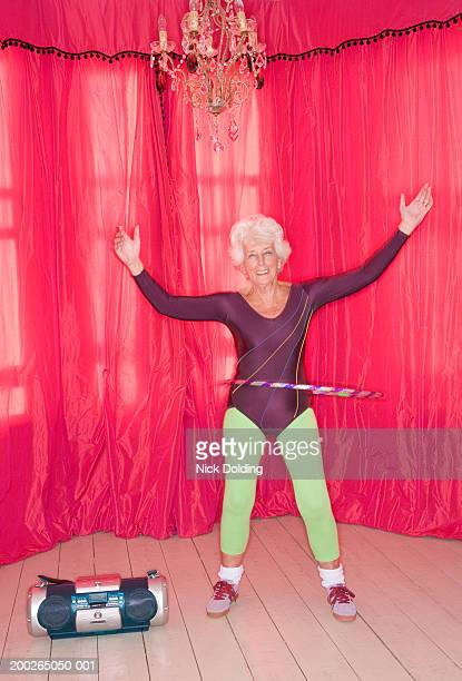senior woman exercising with plastic hoop, smiling, portrait - leotard stock pictures, royalty-free photos & images