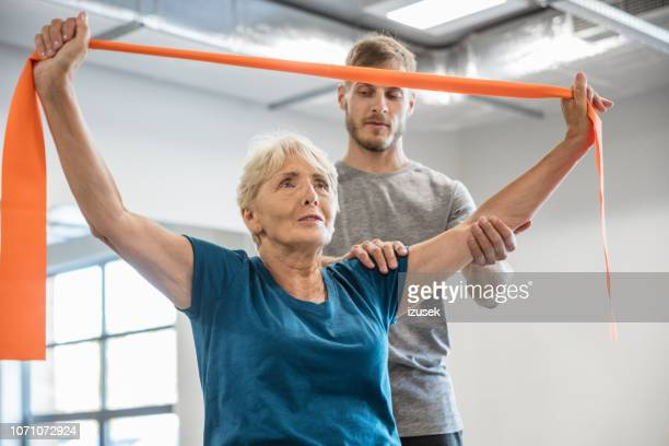 senior woman exercising with resistance band at rehab - izusek stock pictures, royalty-free photos & images