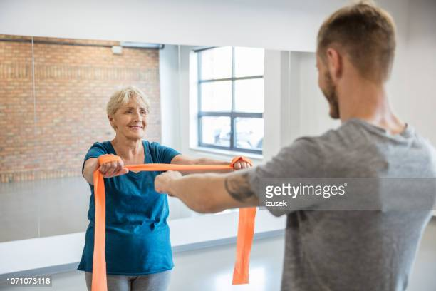 senior woman exercising with resistance band at rehab - drug rehab stock pictures, royalty-free photos & images