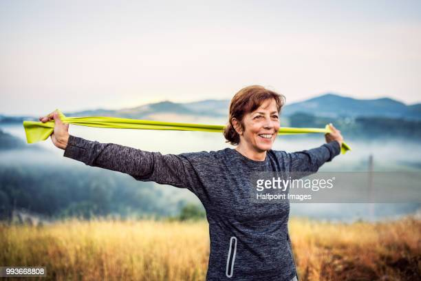 Senior woman exercising with resistance bands outdoors in nature in the foggy morning.