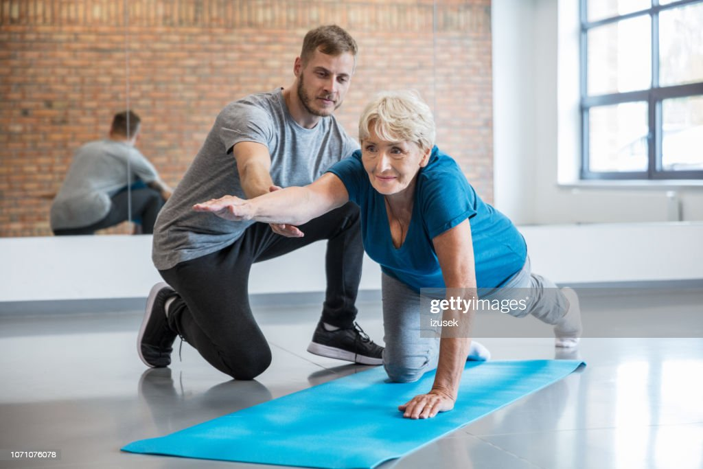 Senior woman exercising with trainer at rehab : Stock Photo