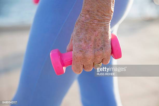 senior woman exercising with weights by beach - old women in pantyhose stock photos and pictures
