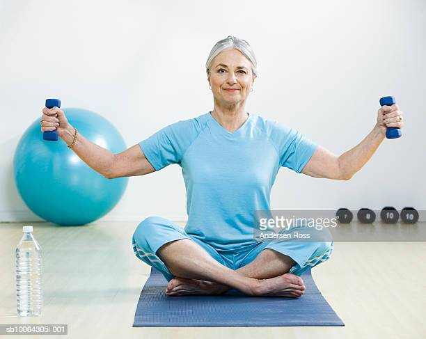 Senior woman exercising with weights in home, portrait