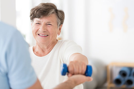 Senior woman exercising with weights 950649706