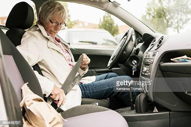 Senior woman fastening seat belt in car