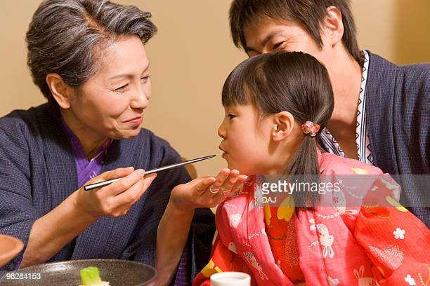 Senior woman feeding granddaughter, smiling