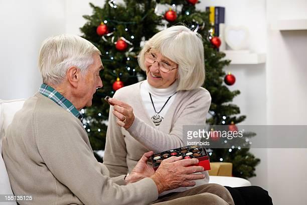 Senior Woman Feeding Her Partner/ Husband Chocolate At Christmas