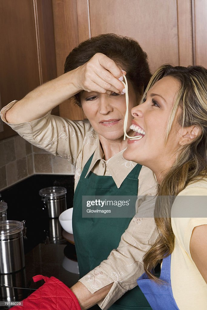Senior woman feeding noodles to her daughter in the kitchen : Stock Photo