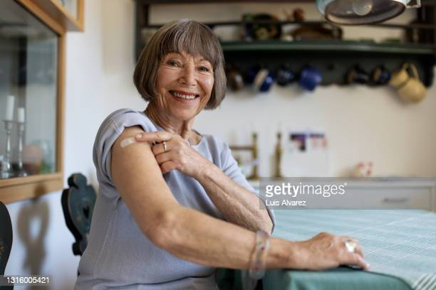 senior woman feeling proud after getting covid-19 vaccine - arm stock pictures, royalty-free photos & images