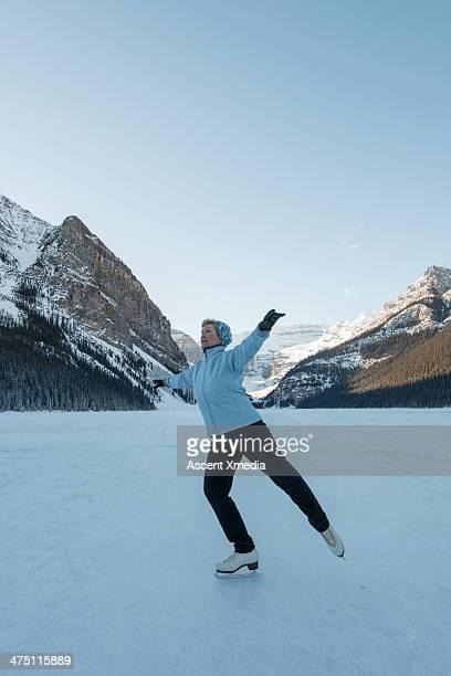 senior woman figure skates on frozen mtn lake - one senior woman only stock pictures, royalty-free photos & images