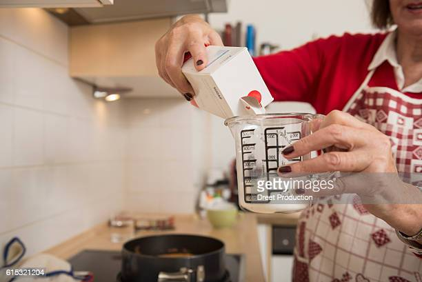 Senior woman filling icing sugar into a measuring cup in kitchen, Munich, Bavaria, Germany