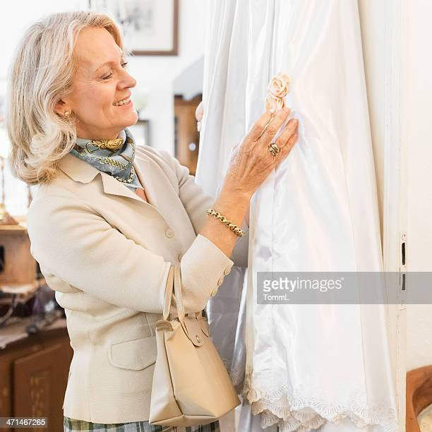 Senior Woman Finding Dress in Antique Store