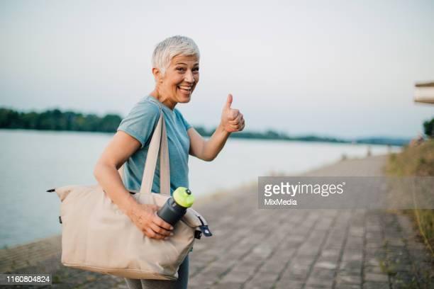 seniorin beendet übung - anstoß sportbegriff stock-fotos und bilder