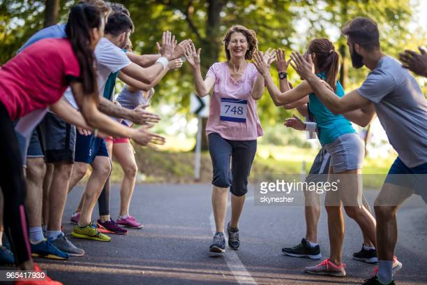 senior woman finishing marathon race and greeting with group of supporters. - marathon stock pictures, royalty-free photos & images