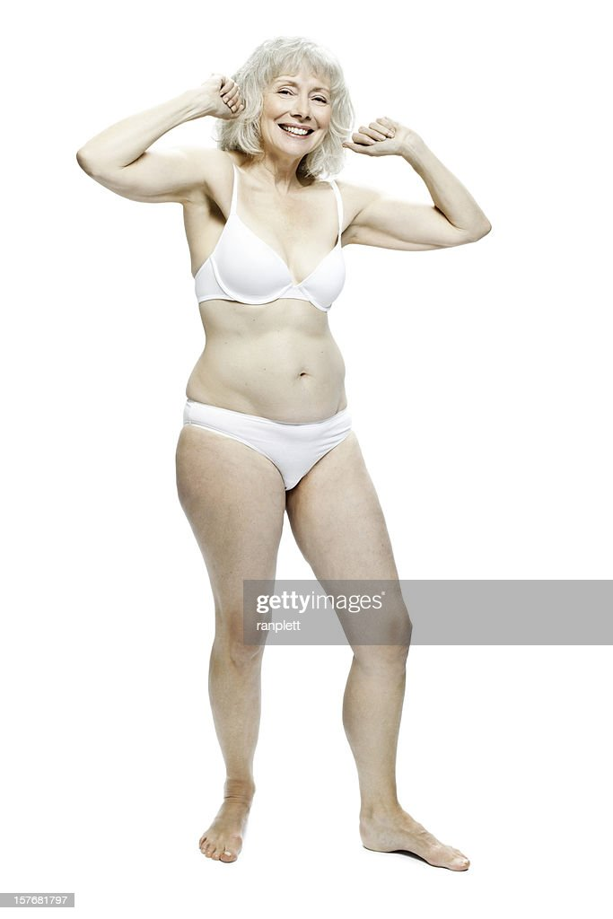 senior woman flexing in underwear isolated stock photo | getty images