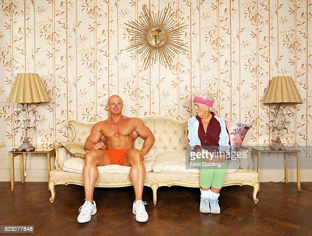 senior woman flirting with bodybuilder on sofa - bodybuilding stock-fotos und bilder