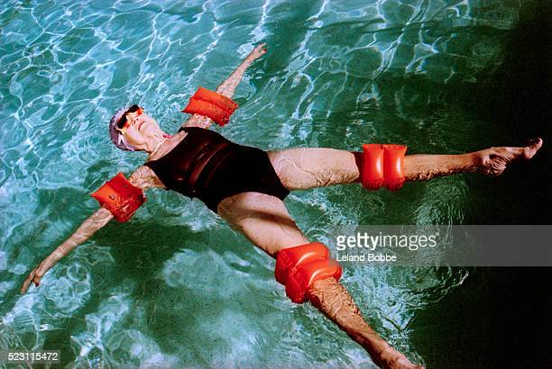 senior woman floating in swimming pool - armband stock pictures, royalty-free photos & images
