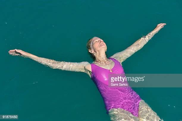 Senior woman floating on water, lake