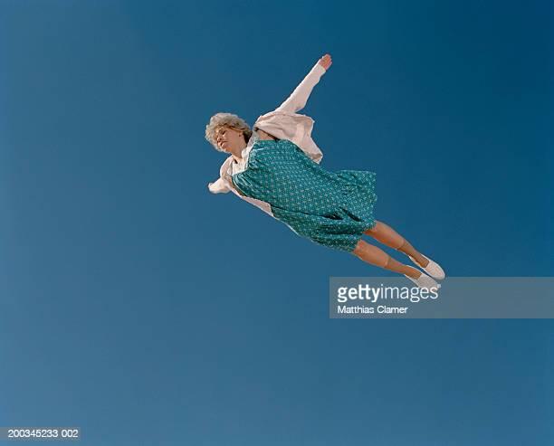 senior woman flying through sky, low angle view - 空中 ストックフォトと画像