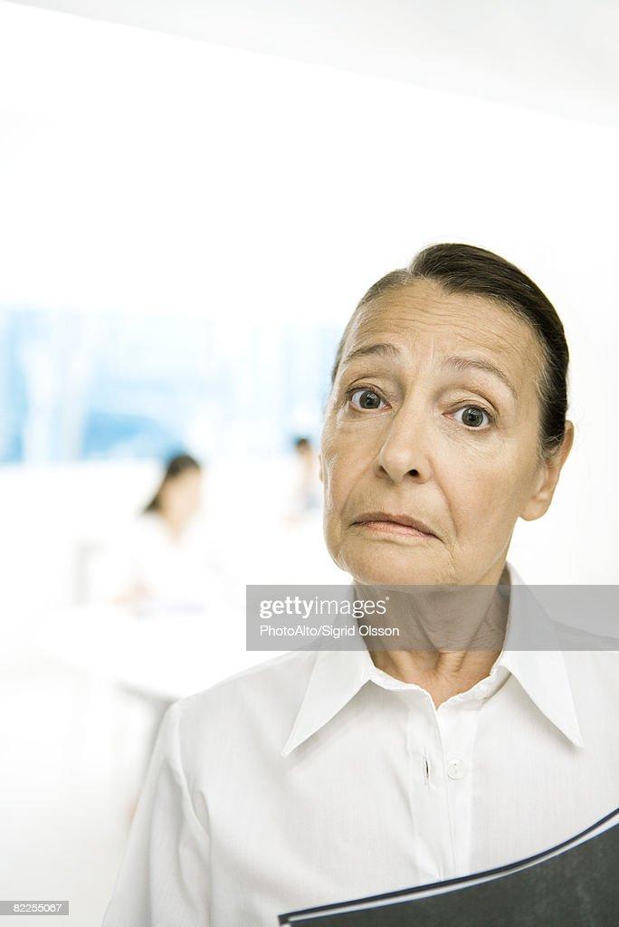 Senior woman frowning at camera, eyebrows raised : Stock Photo
