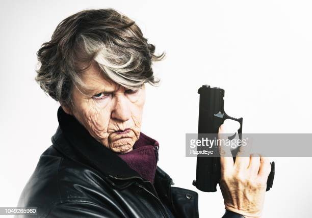 senior woman frowns, holding semi-automatic pistol - frowning stock pictures, royalty-free photos & images