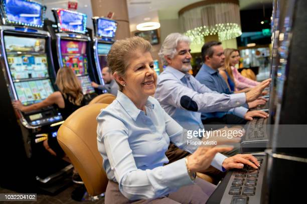 senior woman gambling on slot machine looking very happy - casino stock pictures, royalty-free photos & images