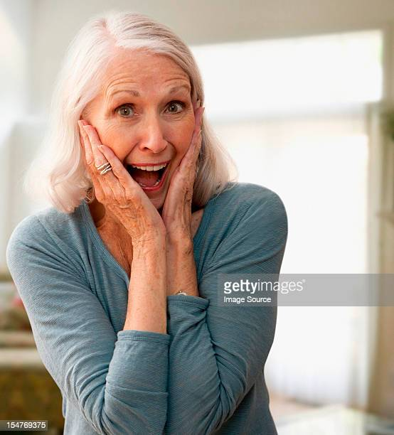 Senior woman gasping with mouth open, touching face