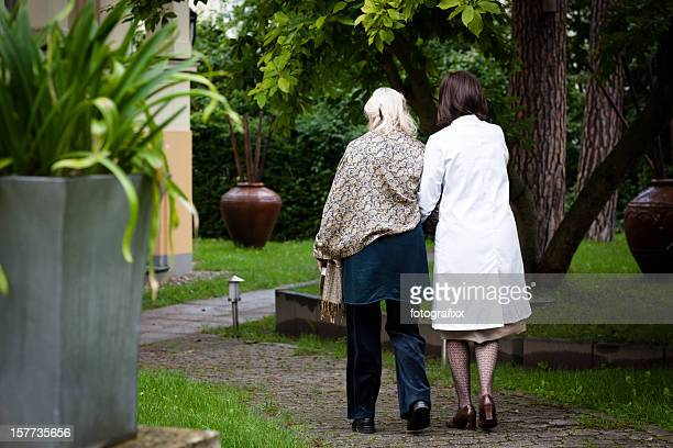 senior woman gets help from nurse for a walk