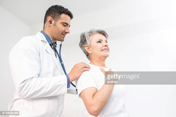 senior woman getting a medical exam at the doctor - heart disease stock pictures, royalty-free photos & images