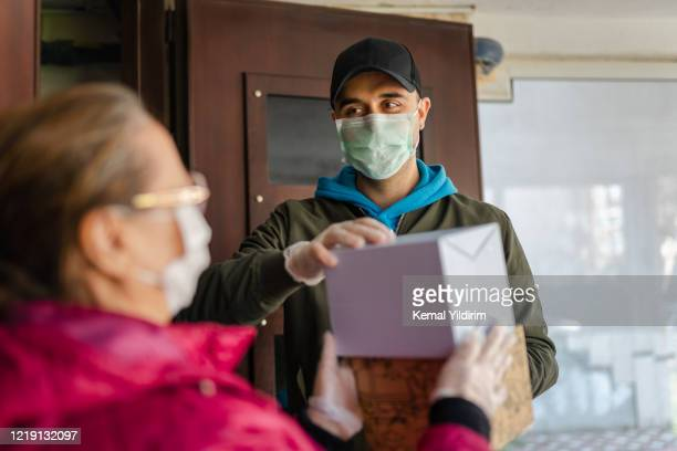 senior woman getting a package from delivery person - turkey middle east stock pictures, royalty-free photos & images