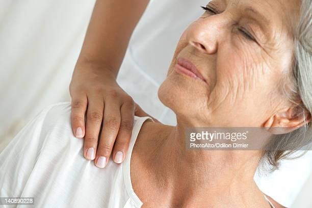 Senior woman getting a shoulder massage, cropped