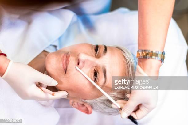 高級女人在美容院被美容師斜著眉毛 - 修眉 個照片及圖片檔