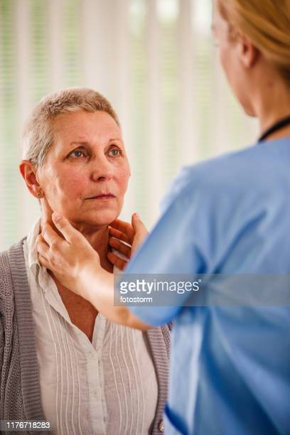 senior woman getting her glands examined - human gland stock pictures, royalty-free photos & images