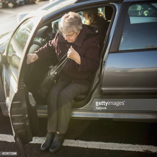 senior woman getting out of a car - getting out stock pictures, royalty-free photos & images