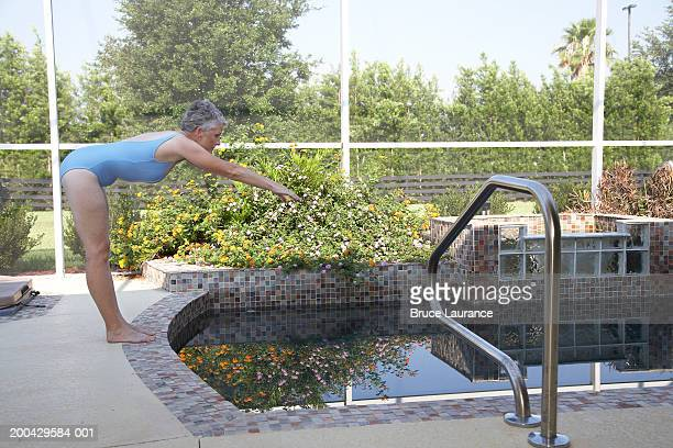 Senior woman getting ready to dive into pool