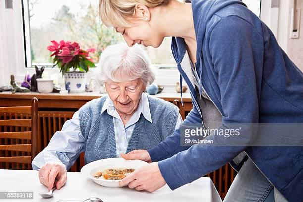 senior Frau immer Suppe serviert von der fürsorgliche