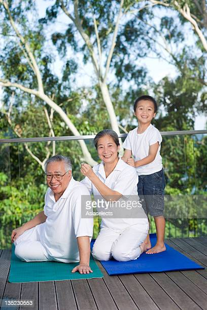 Senior woman giving a massage to a senior man and receiving a massage from her grandson