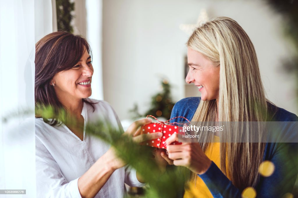 A senior woman giving a present to an adult daughter at home at Christmas time. : Stock Photo