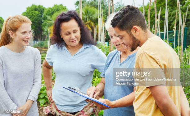 senior woman giving instructions to young volunteers in community garden - compassionate eye foundation stock pictures, royalty-free photos & images