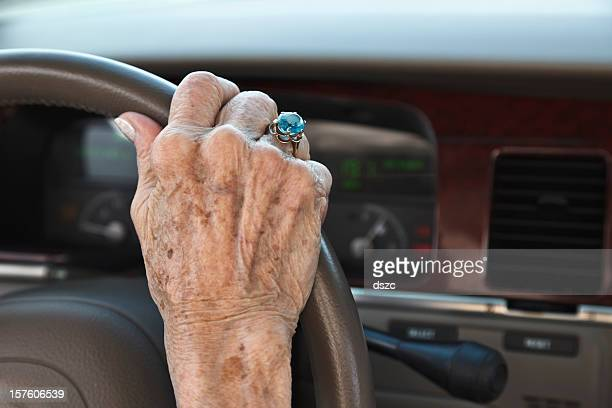 senior woman hand on steering wheel - liver spot stock photos and pictures