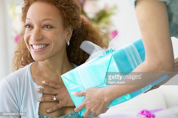 Senior woman handing woman present, smiling, close-up