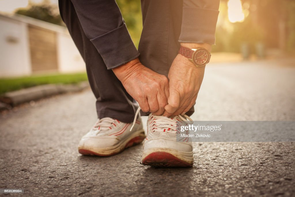 Senior woman hands tying sneakers. Close up. : Stock Photo