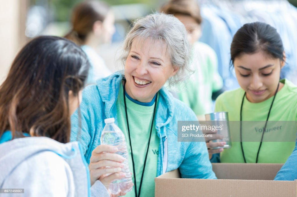 Senior woman hands water bottle to woman during food drive : Stock Photo