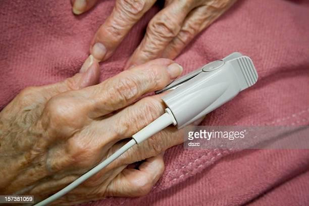 senior woman hands with oxygen sensor in ER hospital bed